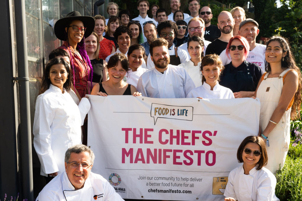 a group of people and chefs in front of a building with a chefs manifesto sign